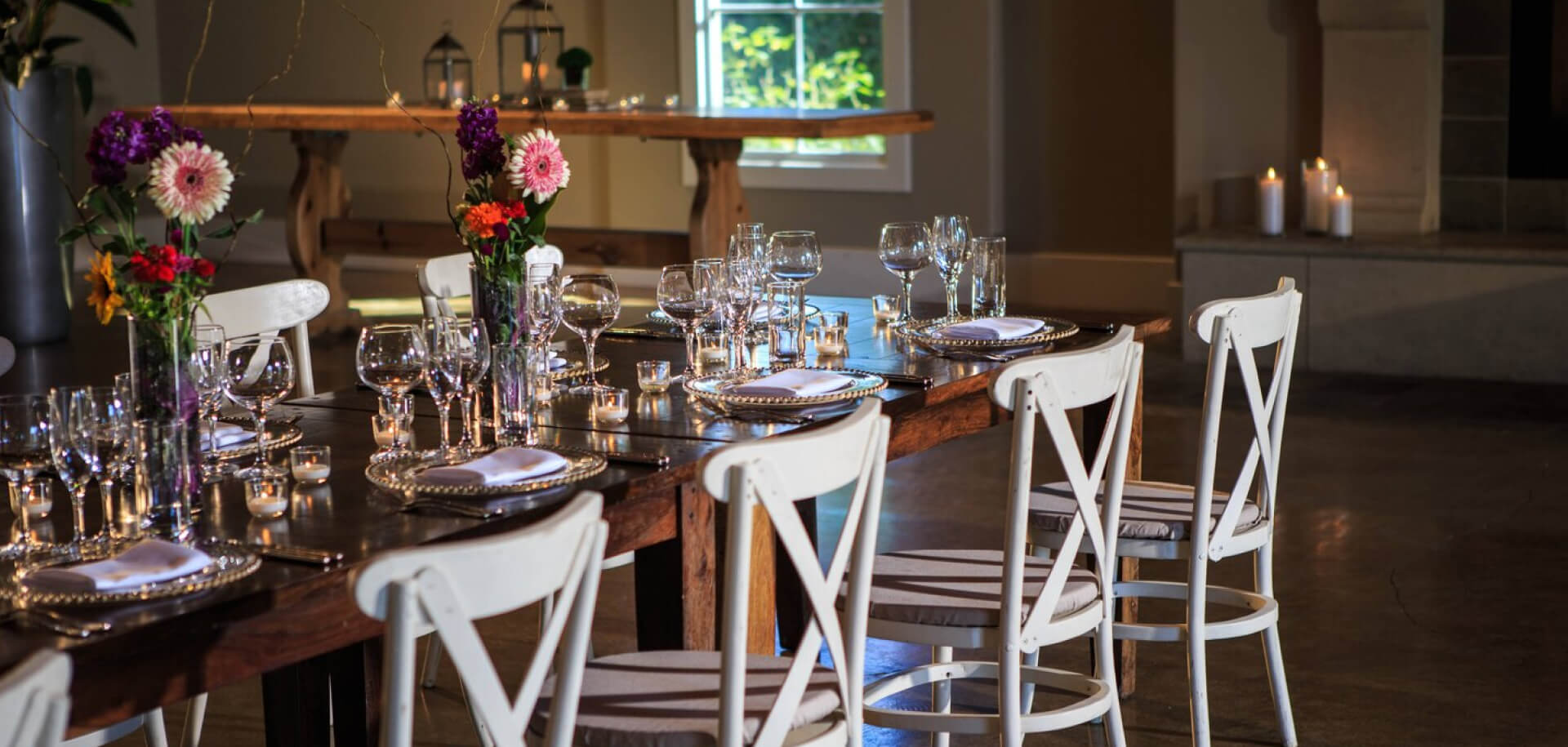 A long dark wood table set with flowers, cutlery and other tableware.