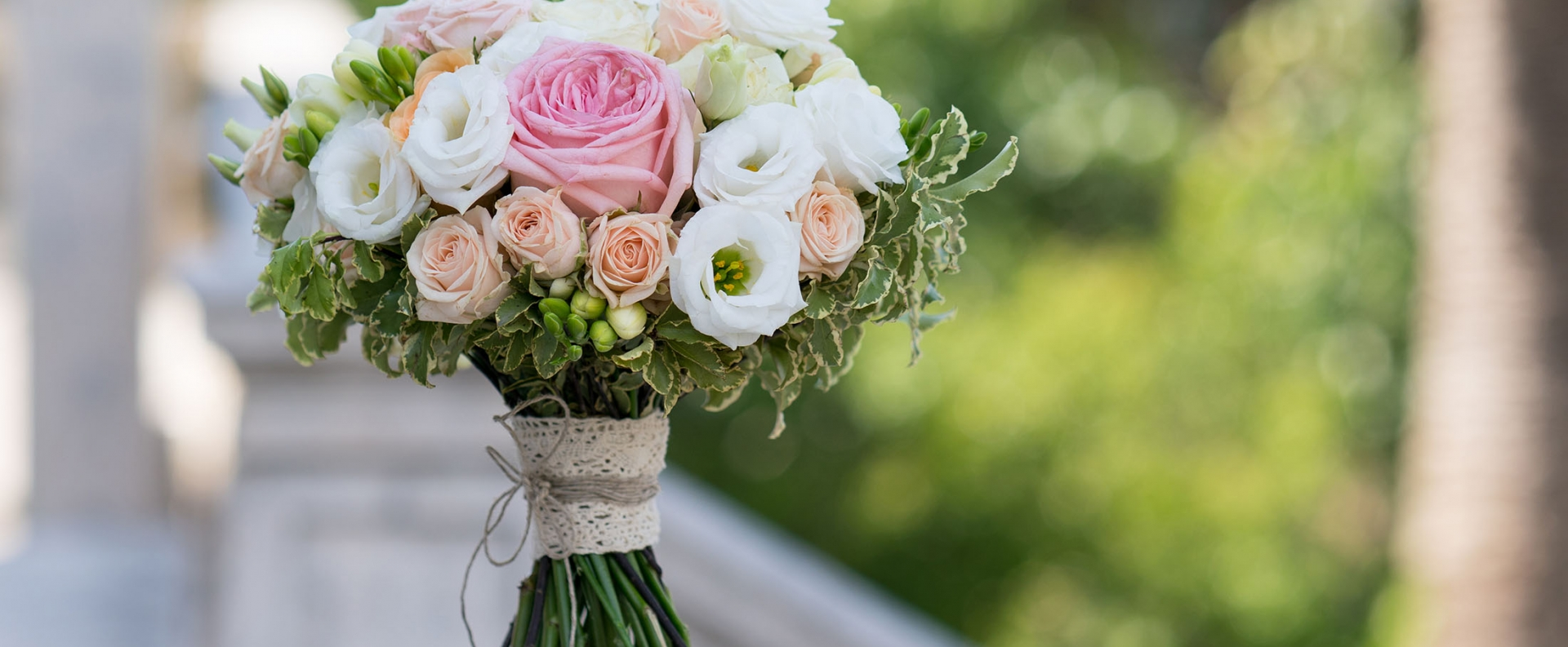 a bridal bouquet of roses, freesia, eustoma standing on a stone background